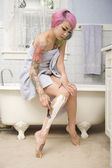 Woman in towel shaving her leg on side of the bathtub — Stock Photo