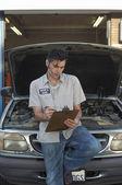 Garage Worker Writing On Clipboard — Stock Photo