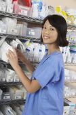 Farmacista femmina in piedi da mensola — Foto Stock