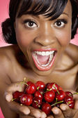 Portrait of woman with hands full of cherries — Stock Photo