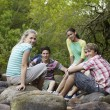 Four Friends Sitting On Stones — Stock Photo