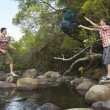 Stock Photo: Young Friends By River Throwing Backpack