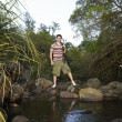 Young Boy Standing By Stream - Stock fotografie