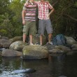Friends Standing On Stones By River — Stock Photo #21942747