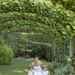 Girls And Bride Squatting Under Ivy Arches - Stock Photo