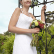 Bride With Bouquet Standing By Gate - Stok fotoğraf