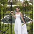 Bride Standing At The Entrance Gate - Stock Photo