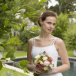 Bride Holding Bouquet At Poolside - Stok fotoğraf