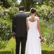 Newlywed Couple Walking In Garden - Stok fotoğraf