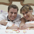 Happy Couple Lying In Bed - Stock Photo