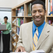 Businessman With Book In Library - Stock Photo