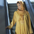 Muslim Woman Standing On Escalator - Stock Photo