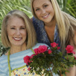 Grandmother And Granddaughter With Rose Plant — Stock Photo