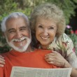 Royalty-Free Stock Photo: Portrait Of A Happy Senior Couple Reading Newspaper