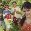 Happy Young Woman With Family In Garden - Stock Photo