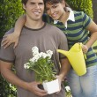 Couple Holding Watering Can And Flower Pot — Stock Photo #21948253