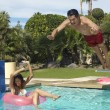 Man Jumping Into Swimming Pool Over Woman On Ring — Stock Photo