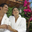Couple In bathrobes Holding Water Bottles — Stock Photo