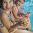 Sisters Drinking Juice By Poolside — Stock Photo