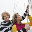 Young Couple Holding Rigging On Sailboat — Stock Photo #21948869