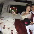 Happy Quinceanera Sitting In Limousine With Partner - Stock Photo