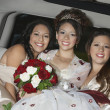 Quinceanera Sitting With Friends In Limousine - Stock Photo