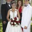 Quinceanera With Parents And Partner Standing In Lawn - Stock Photo