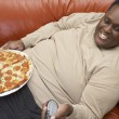 Stock Photo: man watching tv with pizza on lap