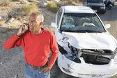 Homme senior sur appel avec une voiture endommagée dans le fond — Photo