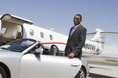 Businessman Standing By Car At Airfield — Stock Photo
