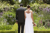 Newlywed Couple Walking In Garden — Stock Photo