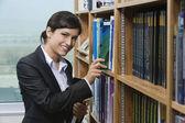 Female Selecting Book From Bookshelf — Stock Photo