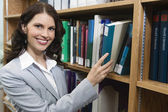 Female Selecting Book From Shelf — Stock Photo
