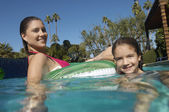 Mother And Daughter Relaxing On Inflatable Raft In Swimming Pool — Stock Photo