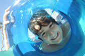 Boy Looking Through Inflatable Ring In Water — Stock Photo