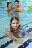 Ragazza carina con i genitori in piscina — Foto Stock