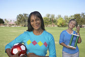 Portrait Of Women Holding Soccer Ball And Trophy In Park — Stock Photo