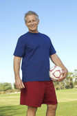 Starší muž drží fotbalový míč v parku — Stock fotografie