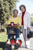 Senior Woman On Motor Scooter With Friend — Stock Photo