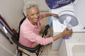 Disabled Senior Woman Doing Laundry At Home — Стоковое фото