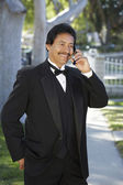 Happy Man In tuxedo Using Cell Phone At Quinceanera — Stock Photo