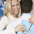 Woman With Christmas Present Hugging Man — Stock Photo #21950587