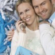 Woman using cell phone with man embracing her by Christmas tree — Stock Photo #21950657