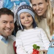 Couple With Son Holding Present In Front Of Christmas Tree — Stock Photo