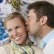 Man Kissing Woman Under Mistletoe - Stock Photo