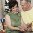 Multiethnic Couple Reading Greeting Card - Stock Photo