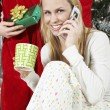 Woman Using Cell Phone In Front Of Man Holding Christmas Present - Stock Photo