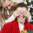Woman Covering Eyes Of Man Holding Present — Stock Photo