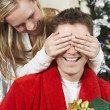 Woman Covering Eyes Of Man Holding Present - Stock Photo