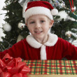 Boy In Santa Claus Outfit Holding Gift - Stock Photo